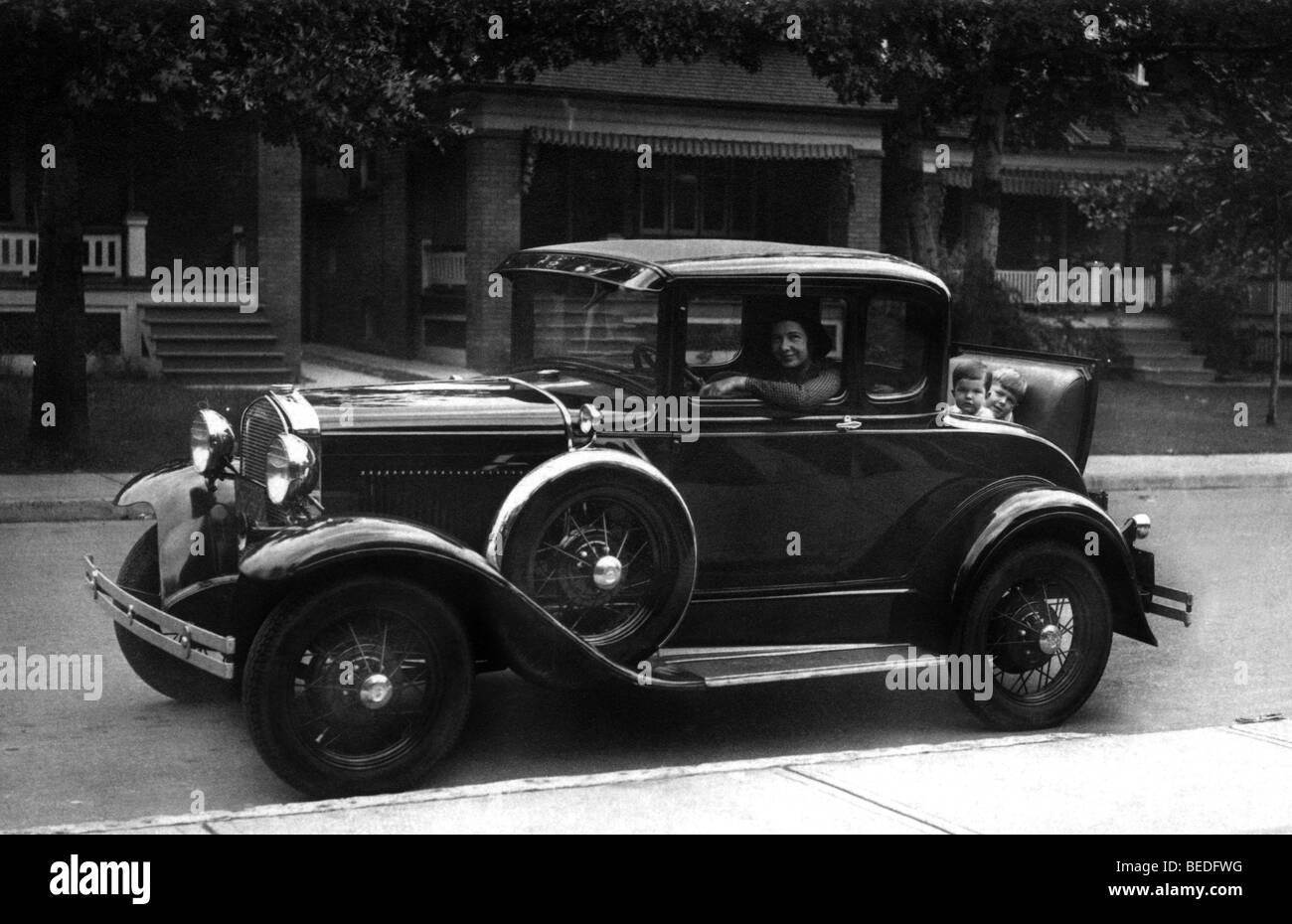 Fotografia storica, donna dietro il volante, i bambini nel tronco, intorno al 1920 Immagini Stock