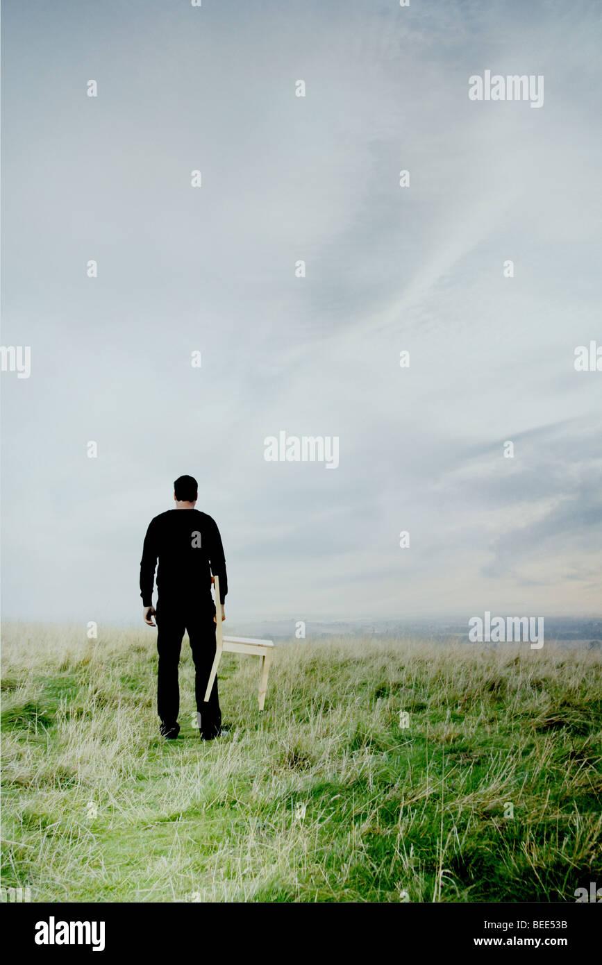 Uomo in piedi sulla collina con una sedia Immagini Stock