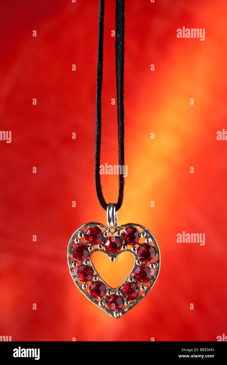 A forma di cuore collane con pietre di rubino e rosso e sfondo dorato Immagini Stock