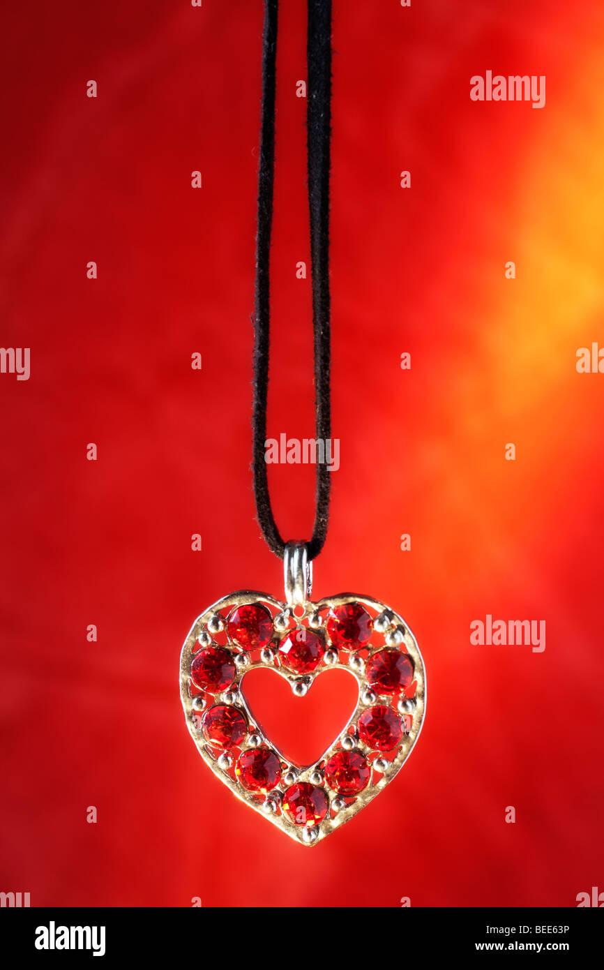 A forma di cuore Collana con pietre di colore rosso e rosso sfondo dorato Immagini Stock