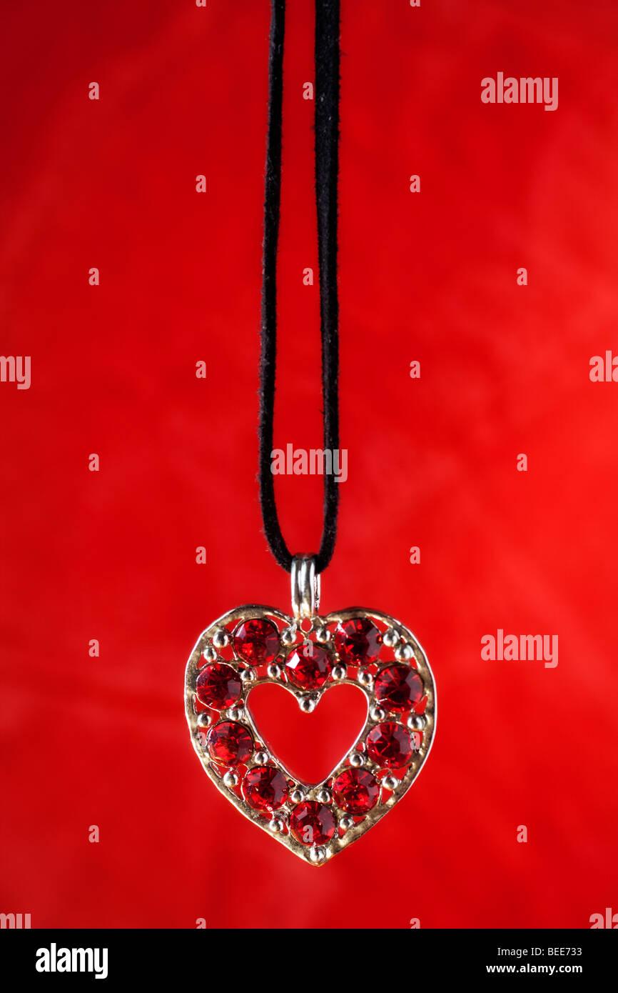 A forma di cuore collane con pietre di rubino e sfondo rosso Immagini Stock