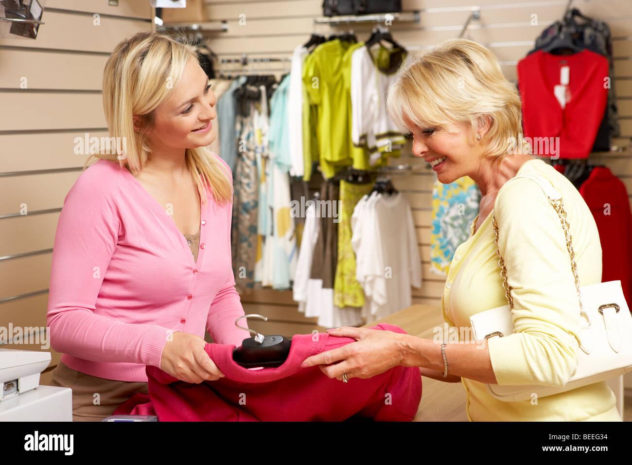 Assistente di vendita con un cliente in negozio di abbigliamento Immagini  Stock 2ff67d4fd99