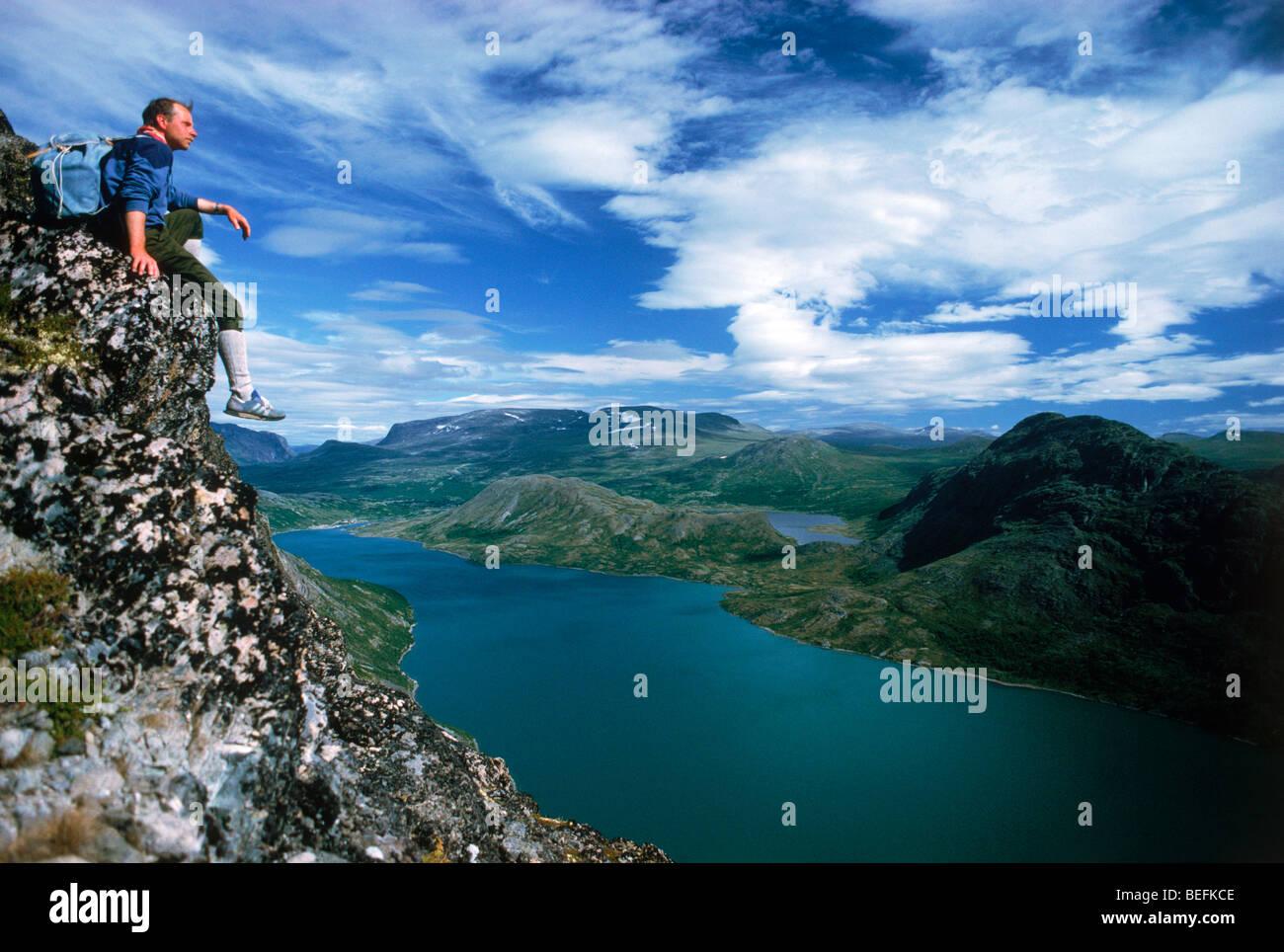 Escursionista seduta al di sopra di Gjende (o) Gjendin Lago in Jotunheimen montagne in Norvegia il parco nazionale Foto Stock