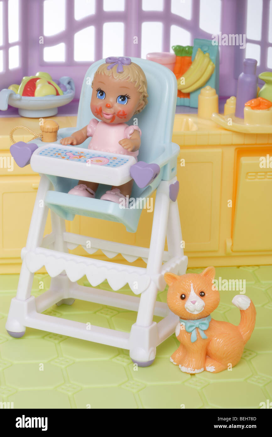 Un giovane bambino bambola in una sedia alta Immagini Stock