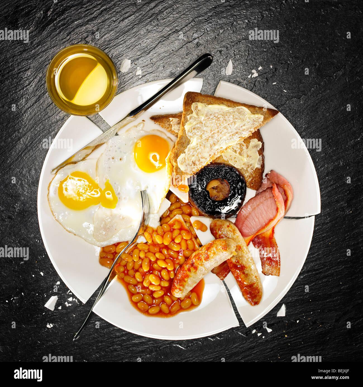 Una colazione completa contenenti uova con pancetta, salsicce, fagioli al forno, i funghi e i toast Foto Stock