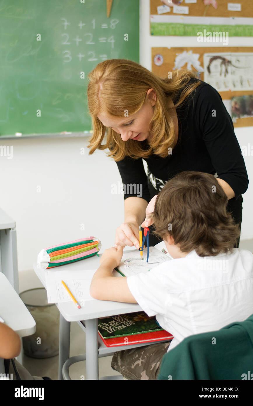 Insegnante che mostra degli studenti elementari come disegnare utilizzando Bussola Immagini Stock