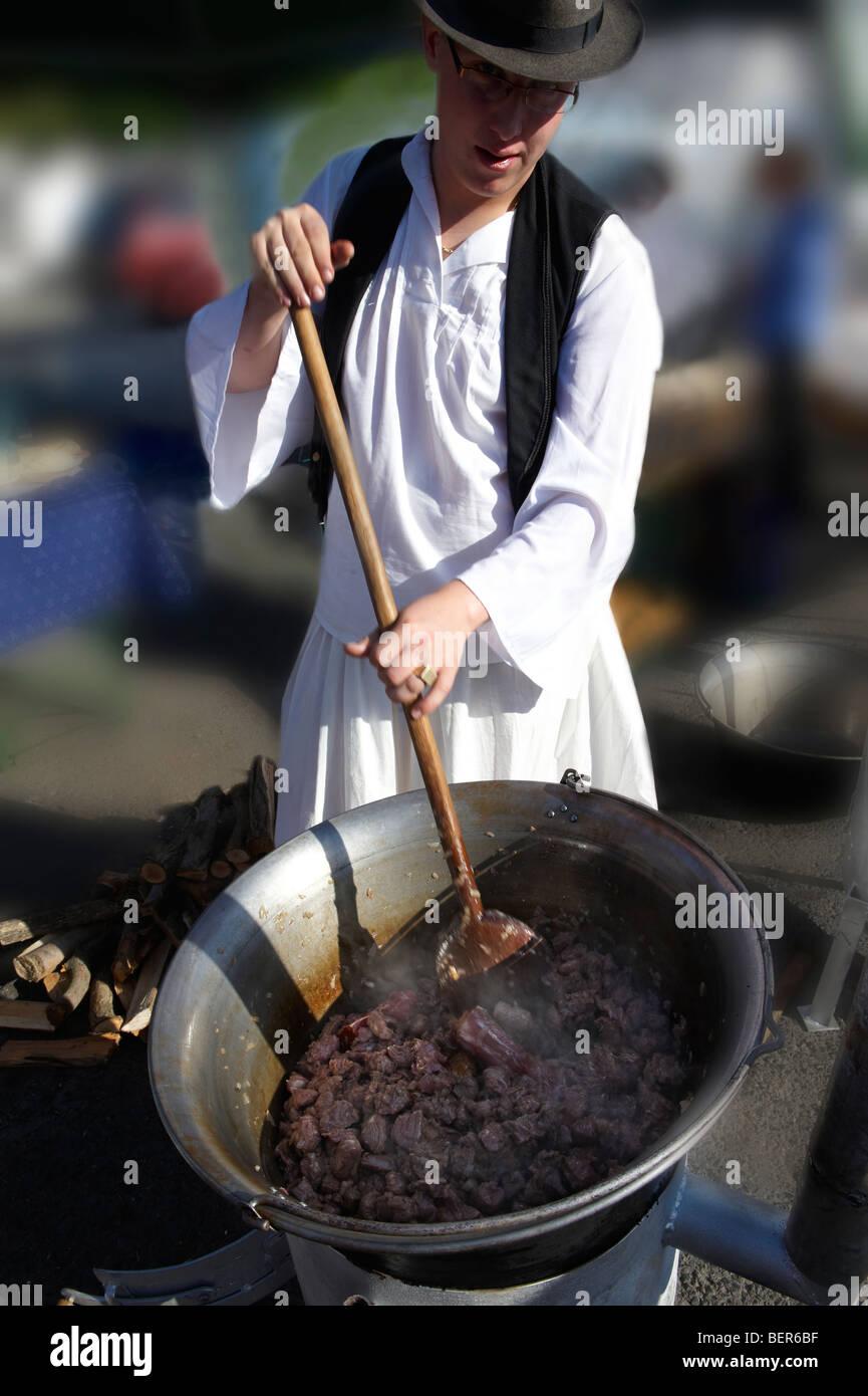 Giovane uomo che indossano il costume tradizionale Bugac Pusza preparare Gulasch - Gyor Gastronomiche Festival Ungheria Immagini Stock