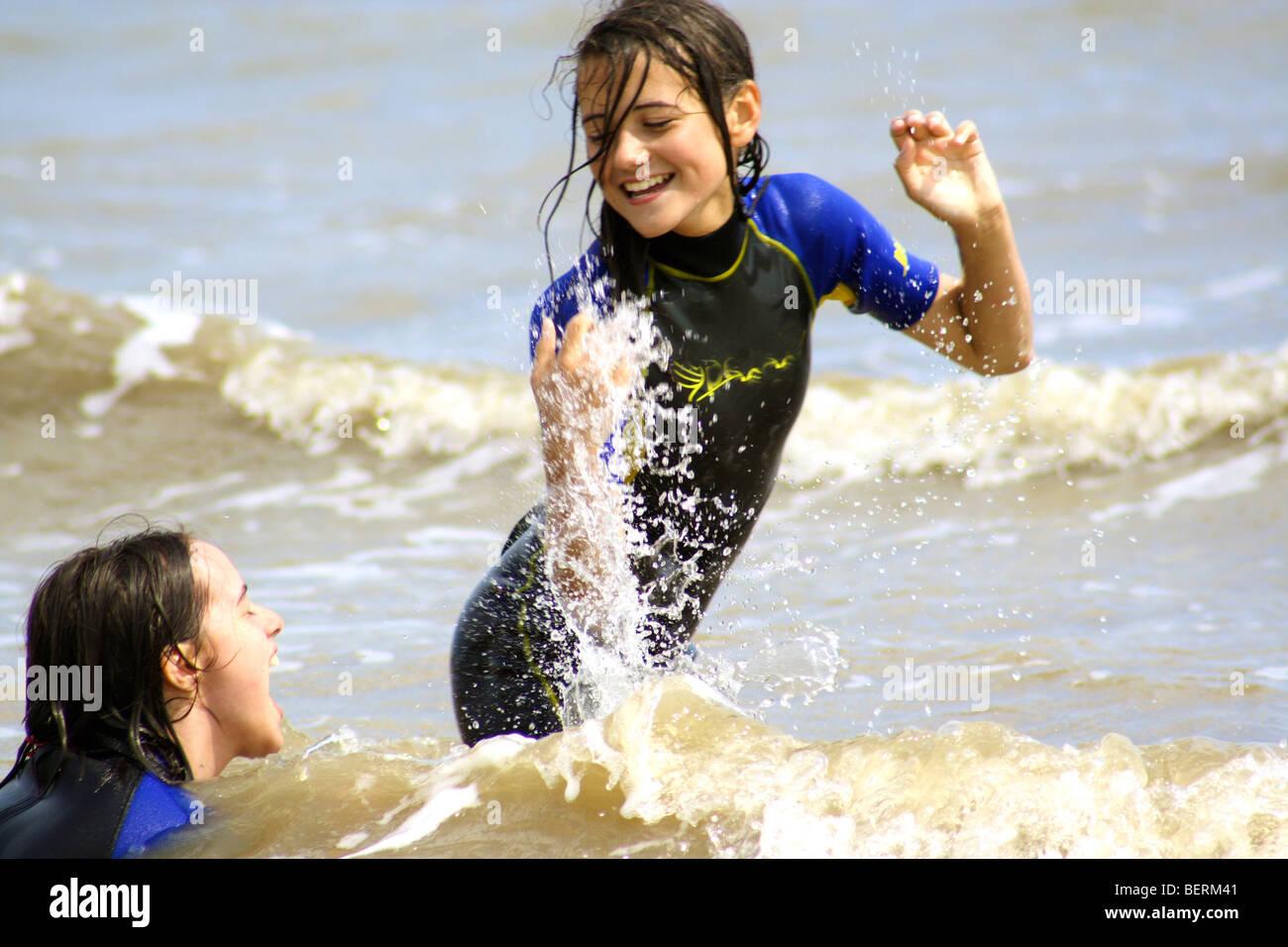 I bambini gli schizzi in mare indossando vestiti bagnati Foto Stock