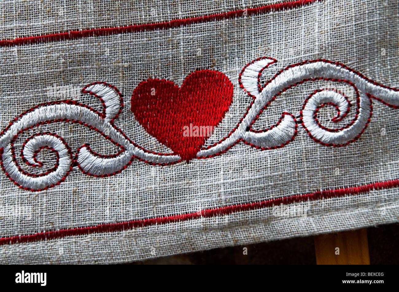 Chiudere la vista sul cuore rosso ricamato sul confine di lino tovaglia Immagini Stock