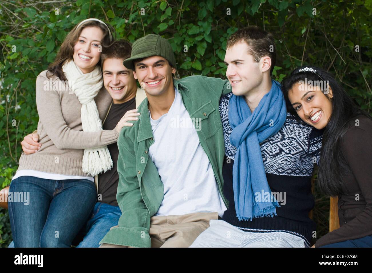 Gruppo di amici seduti insieme e sorridente Immagini Stock