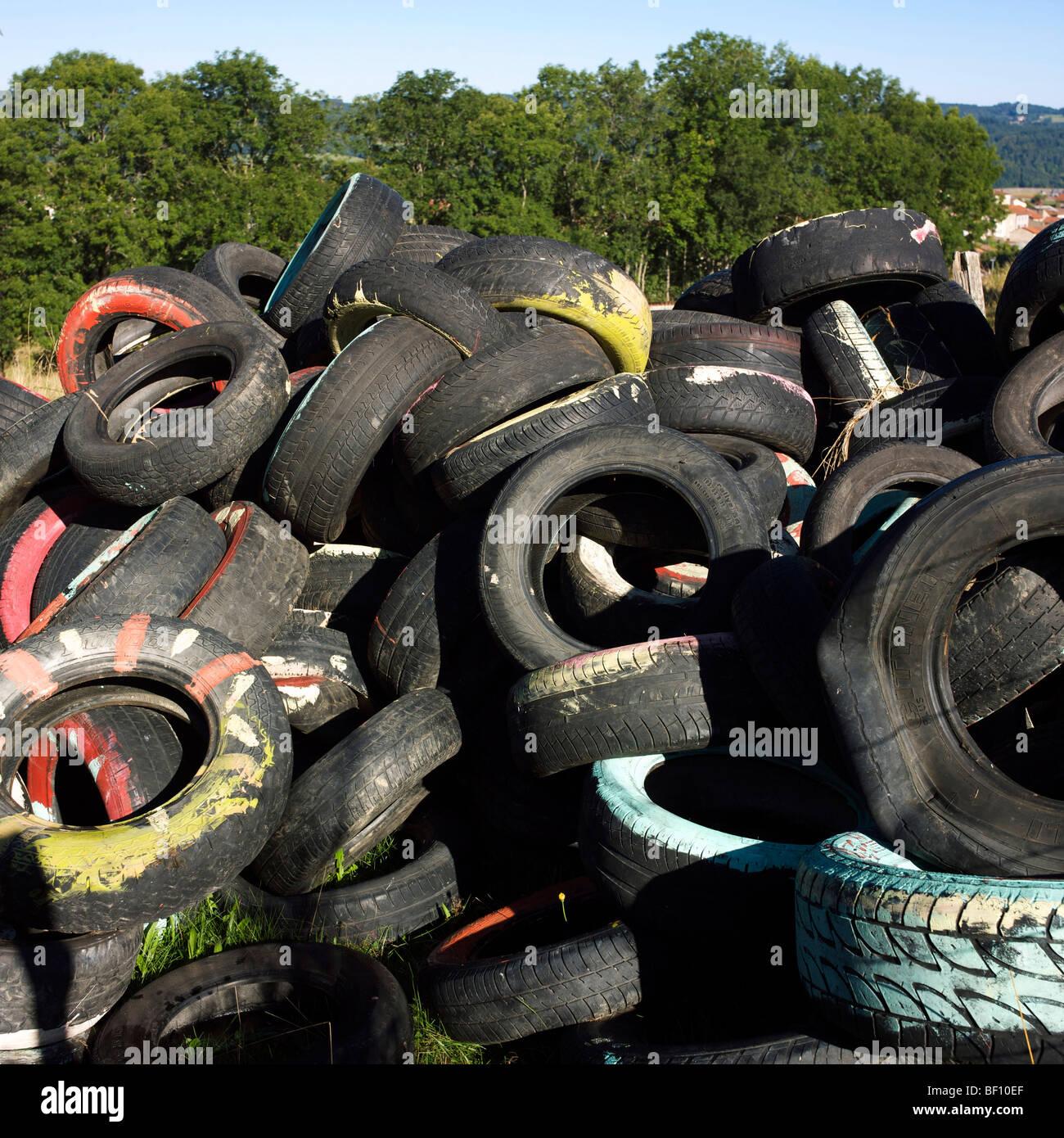 Pila di vecchi pneumatici in gomma in campagna. Immagini Stock