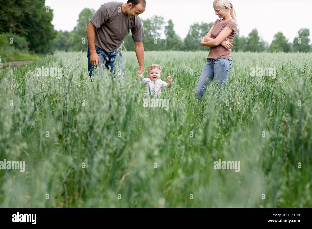 Due i genitori a giocare con la loro figlia in un campo Immagini Stock