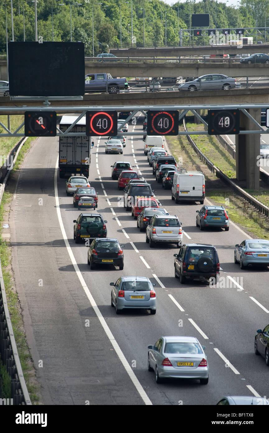 Velocità variabile sezione limite dell'autostrada M42 che mostra il traffico pesante in coda durante le Immagini Stock
