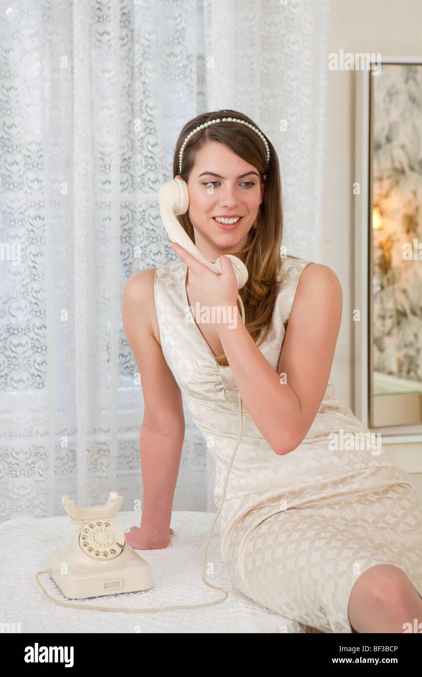 Giovane donna sul vecchio telefono, ridendo Immagini Stock