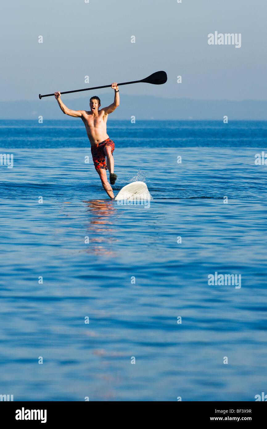 Una metà uomo adulto cadere in un stand up paddle board. Immagini Stock
