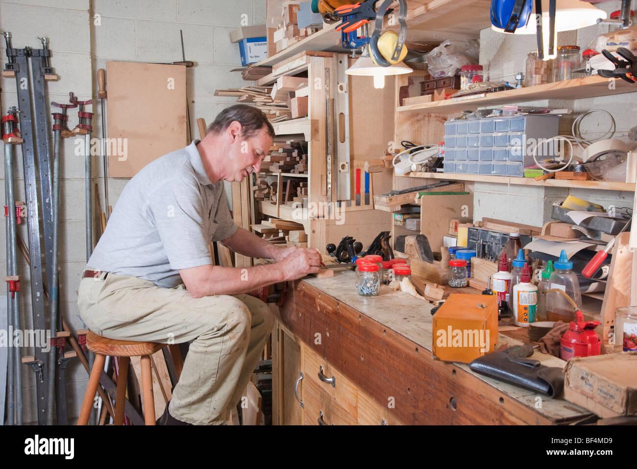 Uomo più anziano al suo banco d'officina Immagini Stock