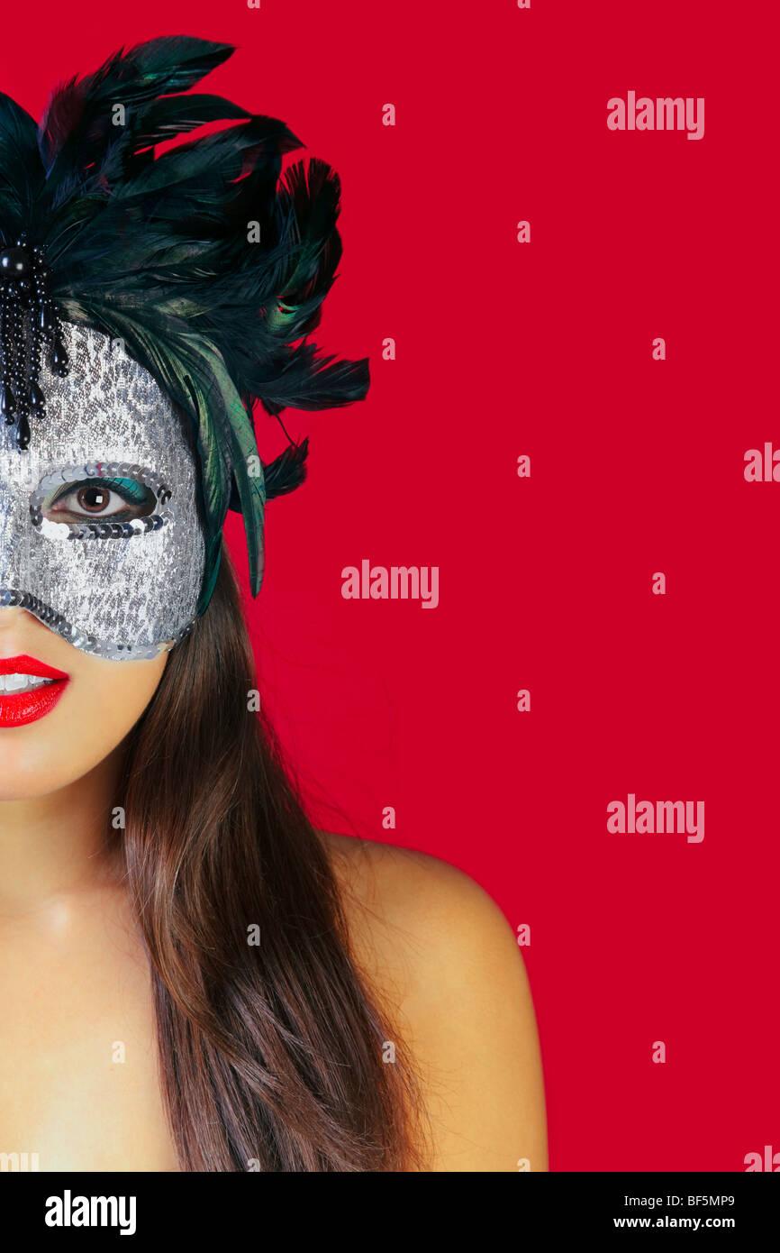 Bella bruna donna che indossa una maschera masqurade contro uno sfondo di colore rosso. Immagini Stock