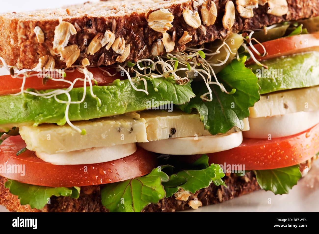 Salute vegetariani sandwich di pane con avocado, formaggio, funghi, lattuga, germogli e pomodori Immagini Stock
