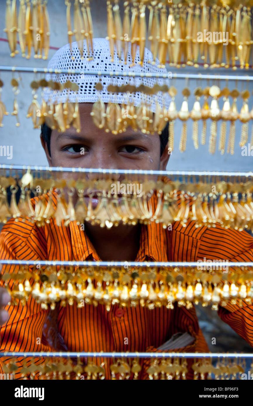 Ragazzo musulmano vendita di gioielli in oro in Ajmer in Rajasthan in India Immagini Stock