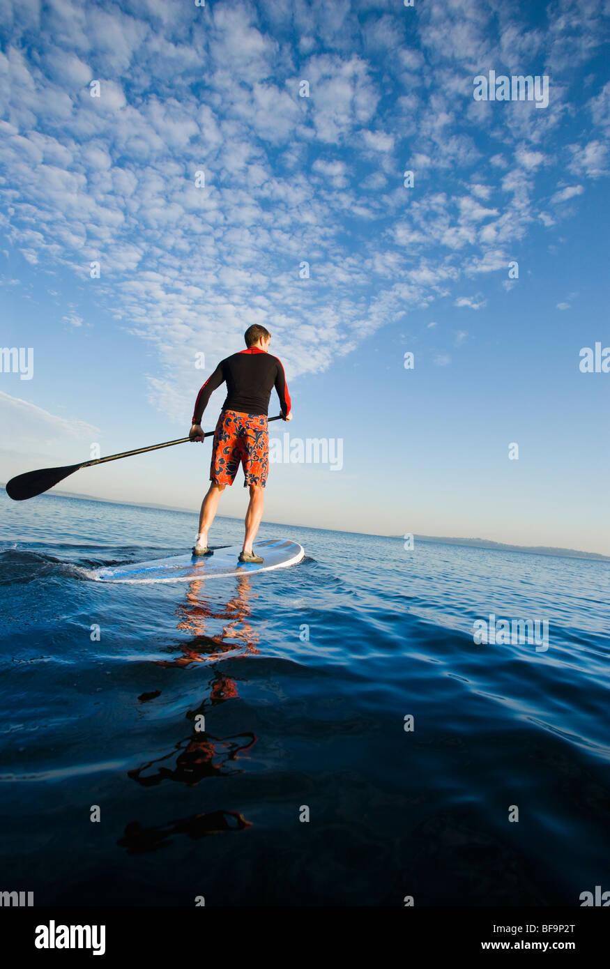 Un uomo atletico paddling out sulla Baia di Elliott / Puget Sound al mattino presto. Immagini Stock