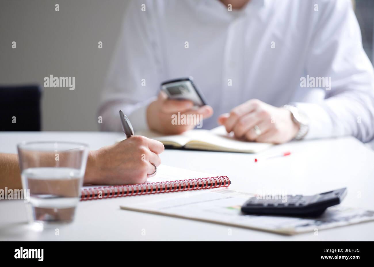 Business meeting prendendo appunti e la ricezione di messaggi di posta elettronica Immagini Stock