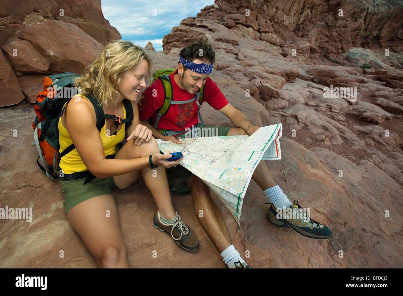 Un sorridente giovane utilizzando una mappa e GPS nel Parco Nazionale di Arches, Utah. Immagini Stock