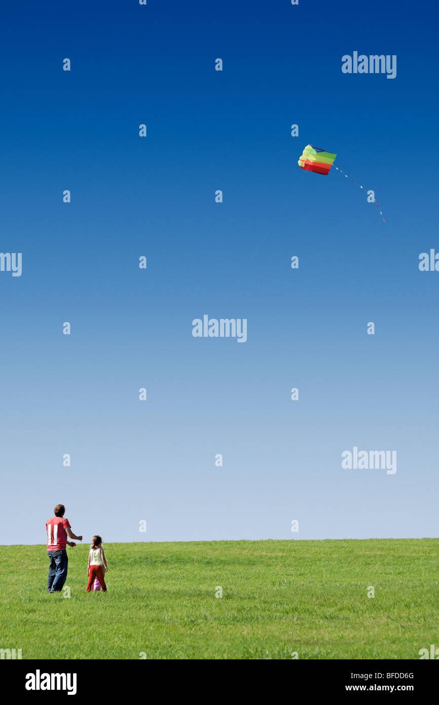 Volare un aquilone padre con i suoi figli Immagini Stock