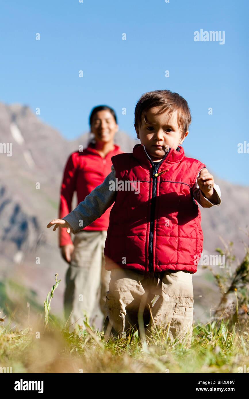 Madre veglia figlio di 14 mesi esplorare prato prendendo break sul viaggio zaino in spalla. Maroon Bells Snowmass Immagini Stock