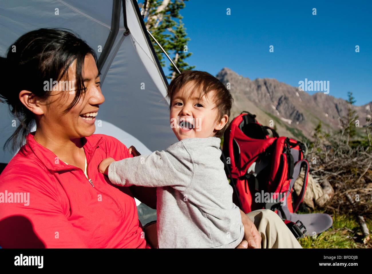 Madre veglia figlio di 14 mesi giocare nel prato di camp. Backpacking trip Maroon Bells in Snowmass deserto fuori Immagini Stock