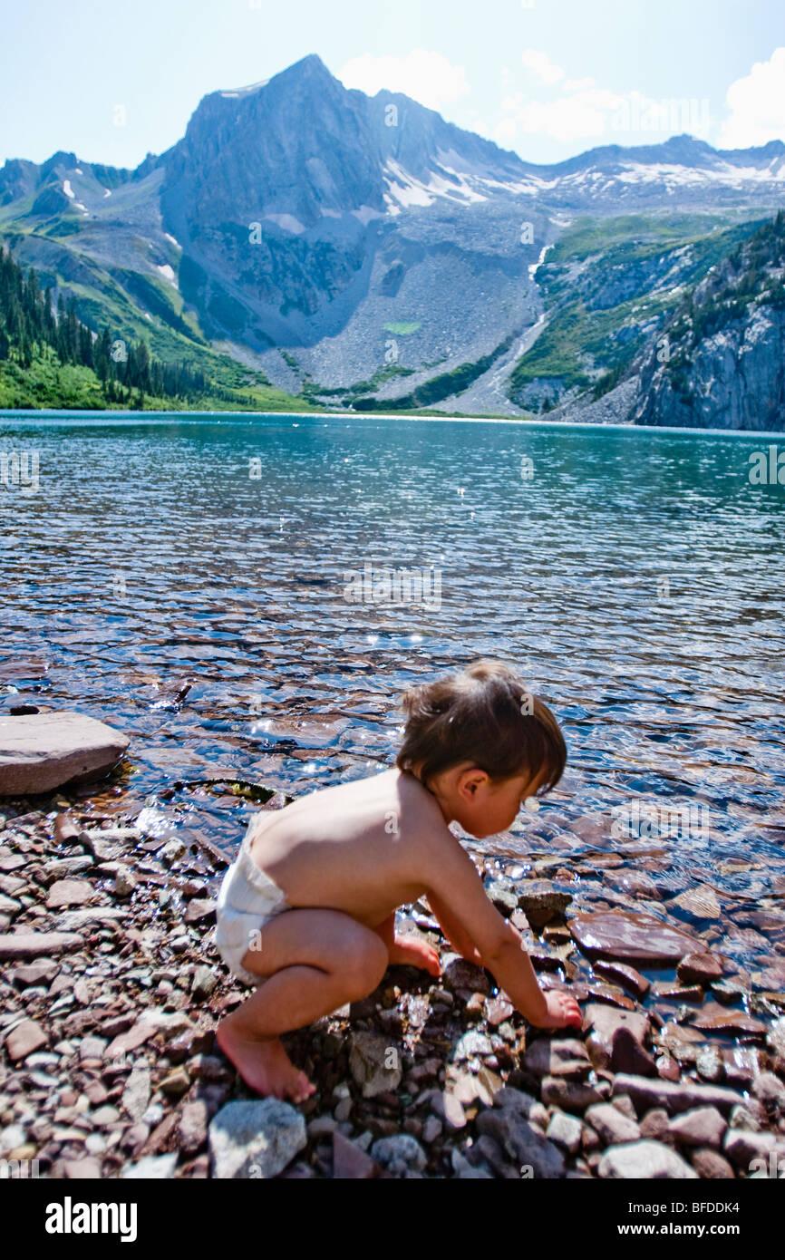 Un mese 14 boy gioca nelle acque del lago Snowmass (10,980ft) con Snowmass montagne sullo sfondo. Immagini Stock