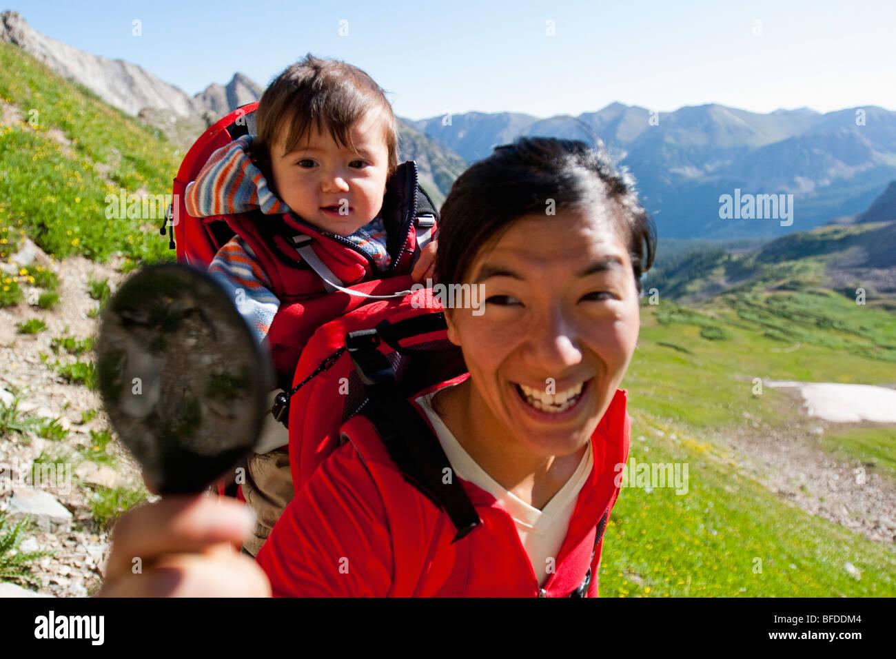 Madre guarda al figlio di 14 mesi con tenuta in mano specchio portato nello zaino. Trail Rider Pass. Riempito di Immagini Stock