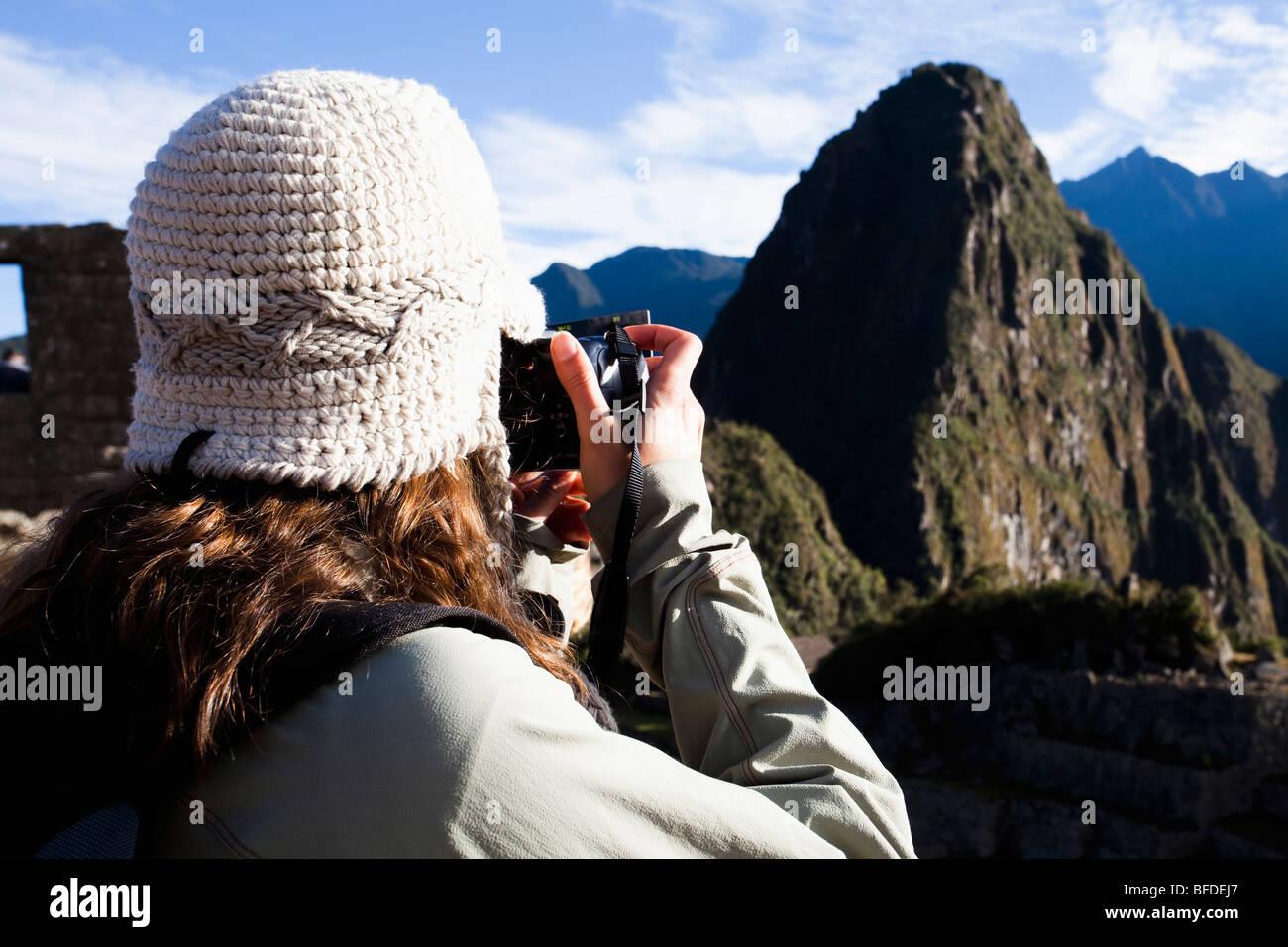 Un adolescente prende una foto di Machu Picchu, le antiche rovine della Valle Sacra del Perù. Immagini Stock