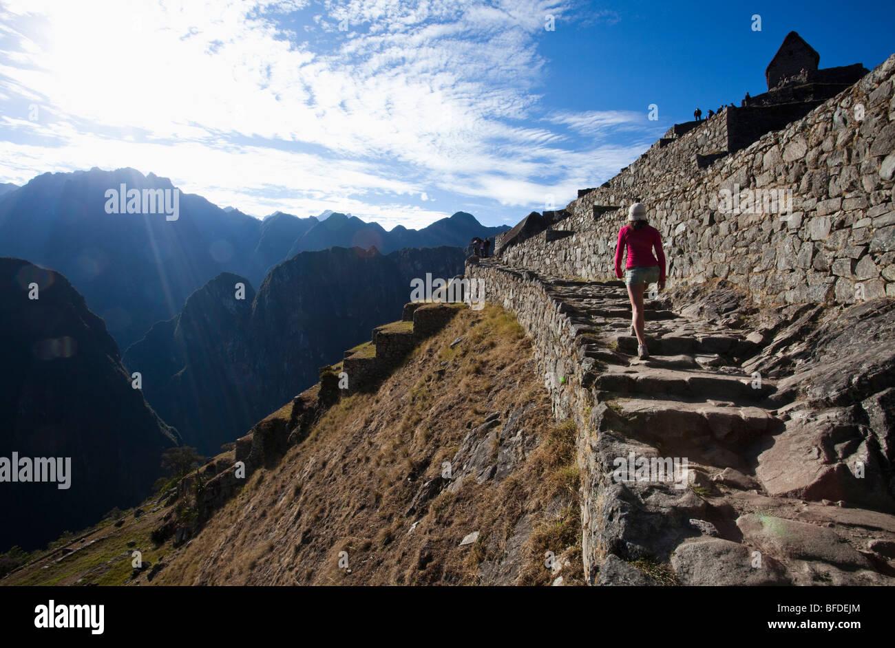 Un adolescente cammina su una scalinata antica che si affaccia su di una ripida valle come lei visita il sito di Immagini Stock