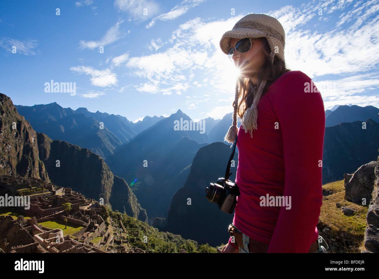 Giovane ragazza sta con la telecamera intorno al suo collo che si affaccia su di una ripida Valle, il Rising Sun, Immagini Stock