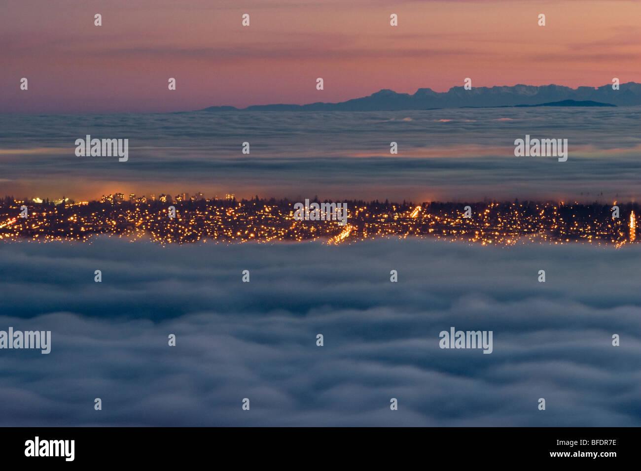 Vancouver e Lower Mainland parzialmente coperta di nebbia e nuvole al tramonto. West Vancouver, British Columbia, Immagini Stock