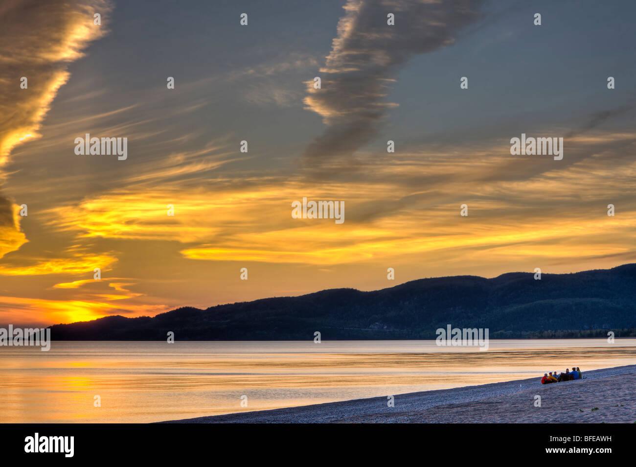 Gruppo di persone sedute sulla spiaggia nella baia di Agawa al tramonto, Lago Superiore, Lago Superior parco provinciale, Immagini Stock