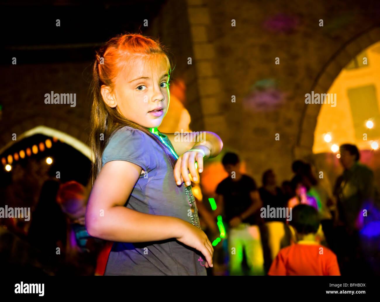 Ragazza giovane discoteca in Castillones town square con luci colorate Immagini Stock