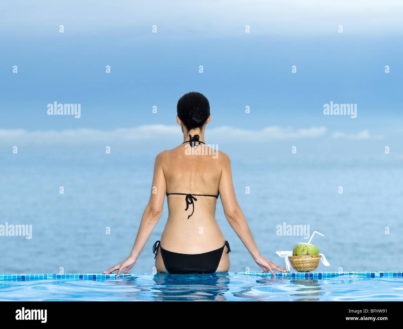 Donna siiting su un bordo di un piscina guardando il mare Foto Stock