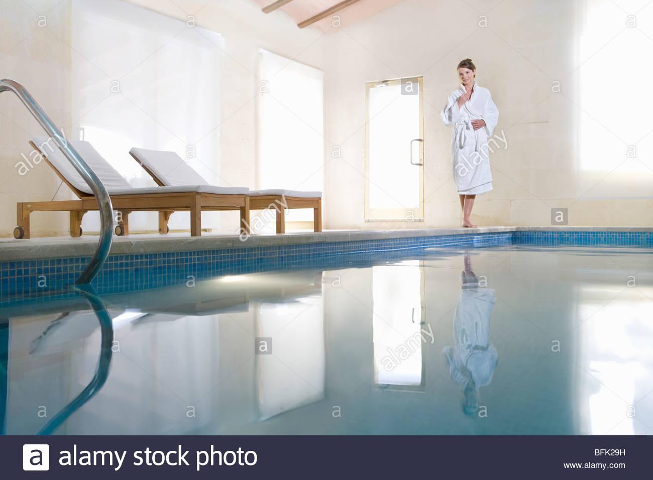 Donna in accappatoio in piedi sul bordo della piscina Immagini Stock