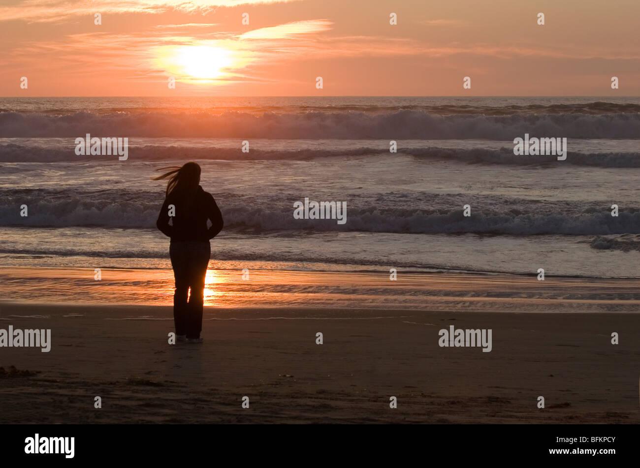 Un anonimo donna visto in silhouette in piedi su una spiaggia al tramonto, i suoi capelli al vento. Foto Stock