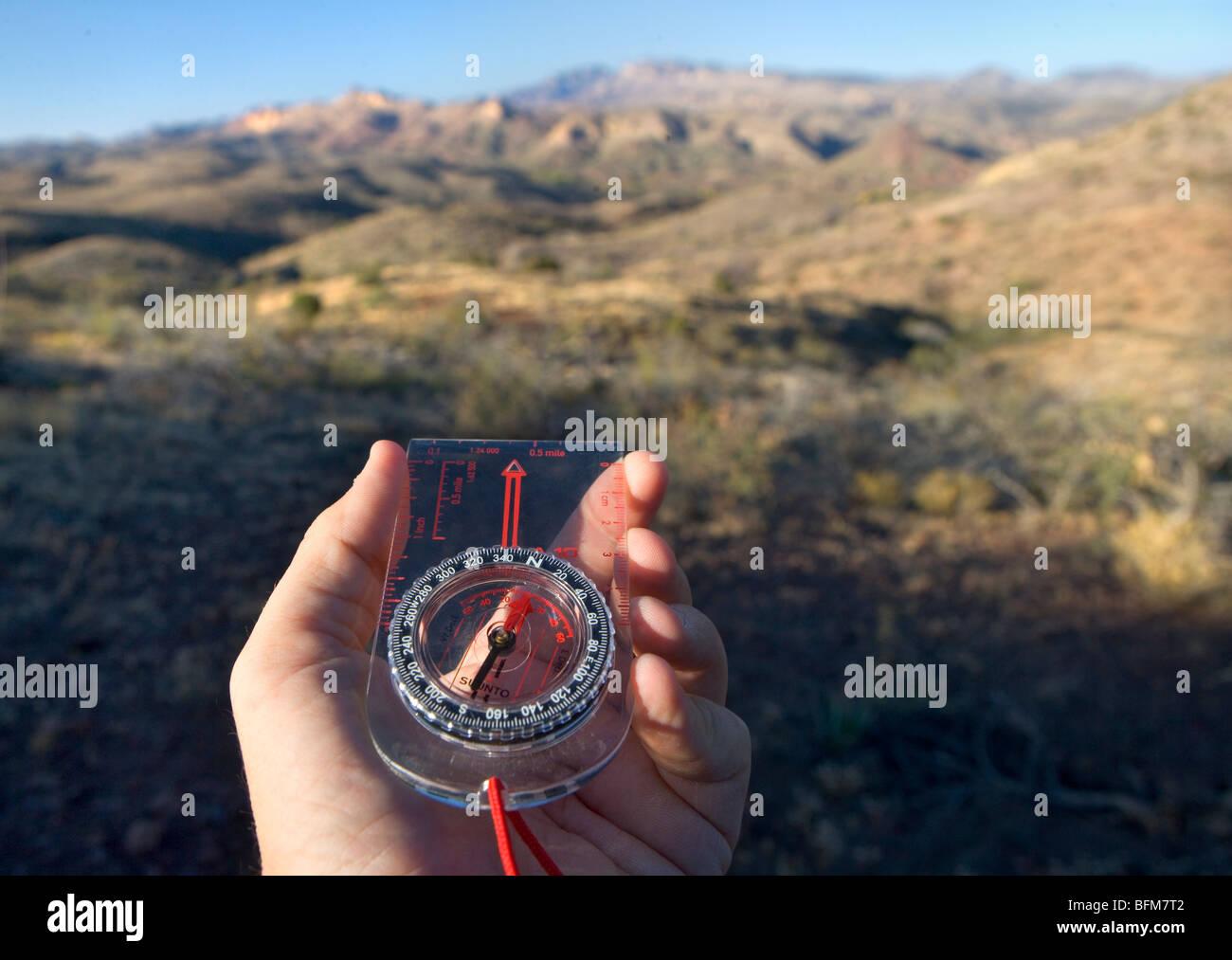 Guardando un escursionismo bussola durante le escursioni. Immagini Stock