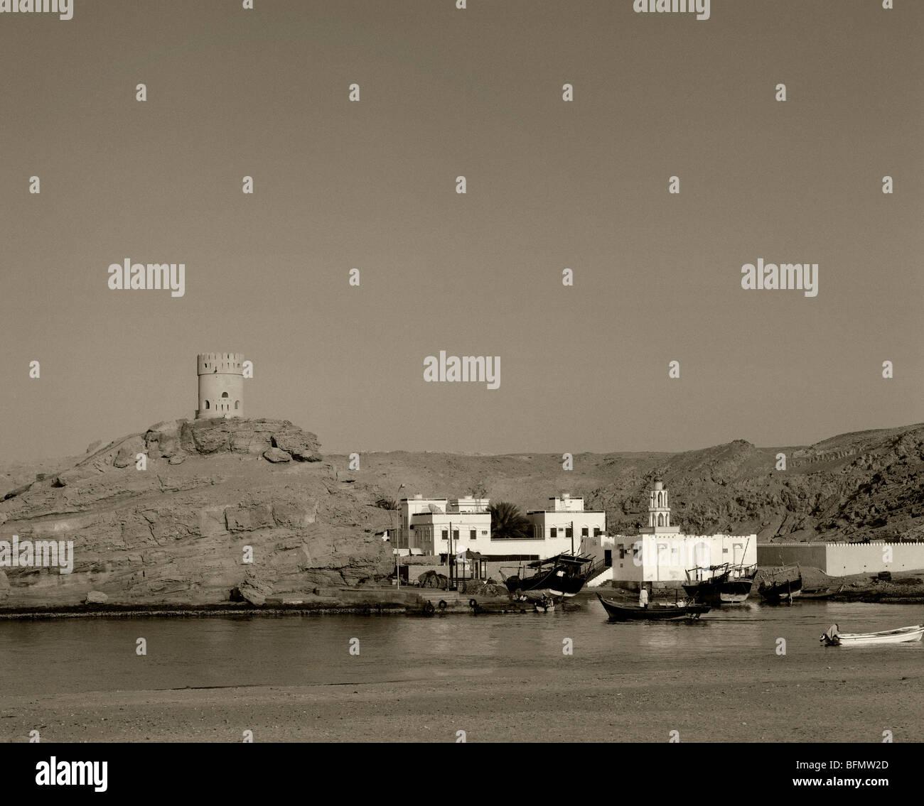Oman, Sur. Una torre di vedetta guarda le bianche case del villaggio di Al Ayja Immagini Stock