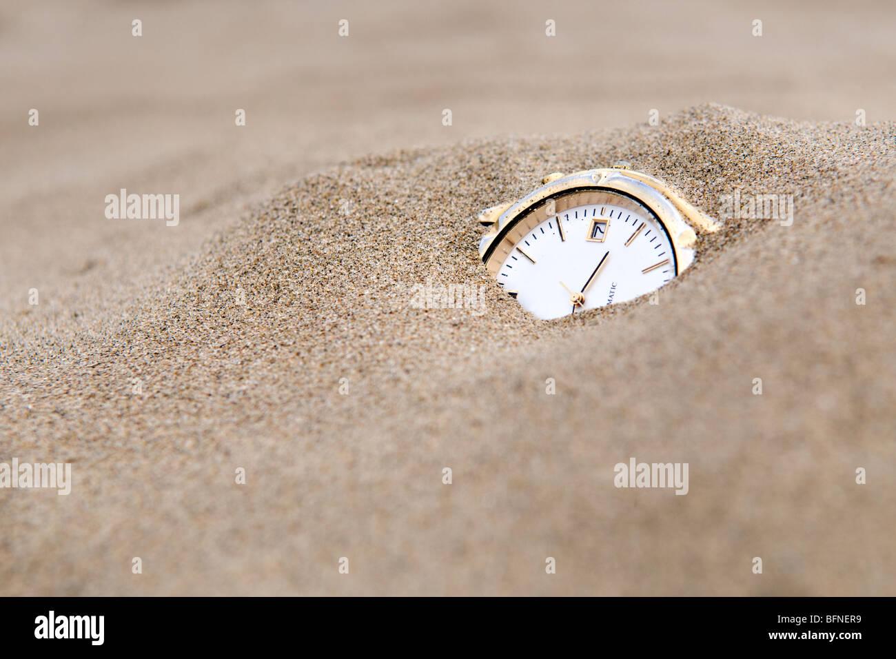 Orologio sepolto in sabbia presi per raffigurare le sabbie del concetto di tempo Immagini Stock
