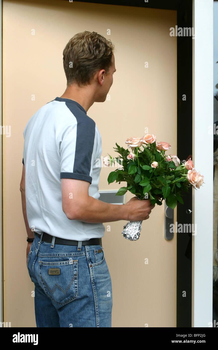 Vestiti Casual Uomo con bouquet di fiori davanti alla porta di casa Immagini Stock
