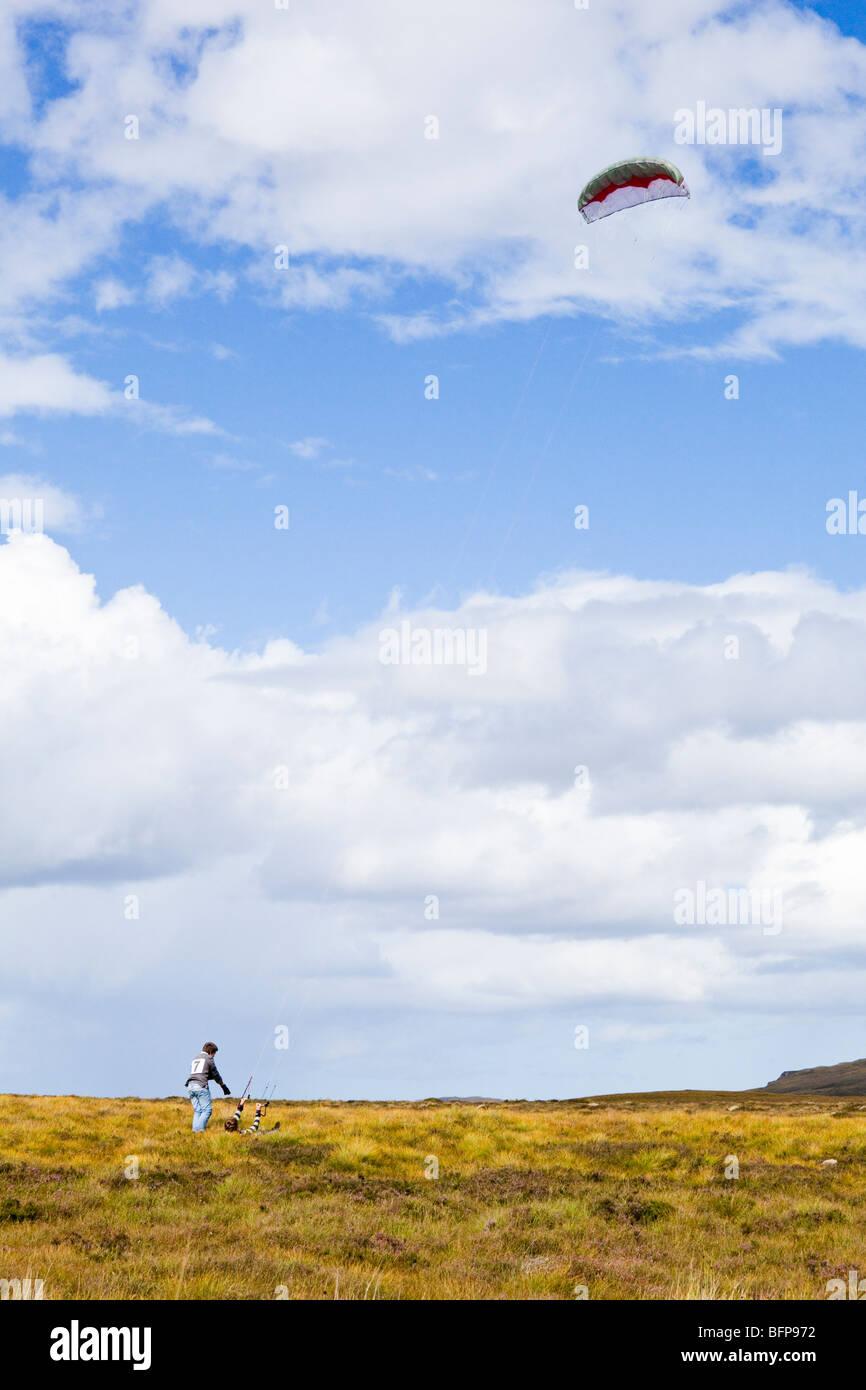 Due fratelli che lottano per volare un aquilone di potenza in condizioni di vento forte sulla brughiera est di Syre, Immagini Stock