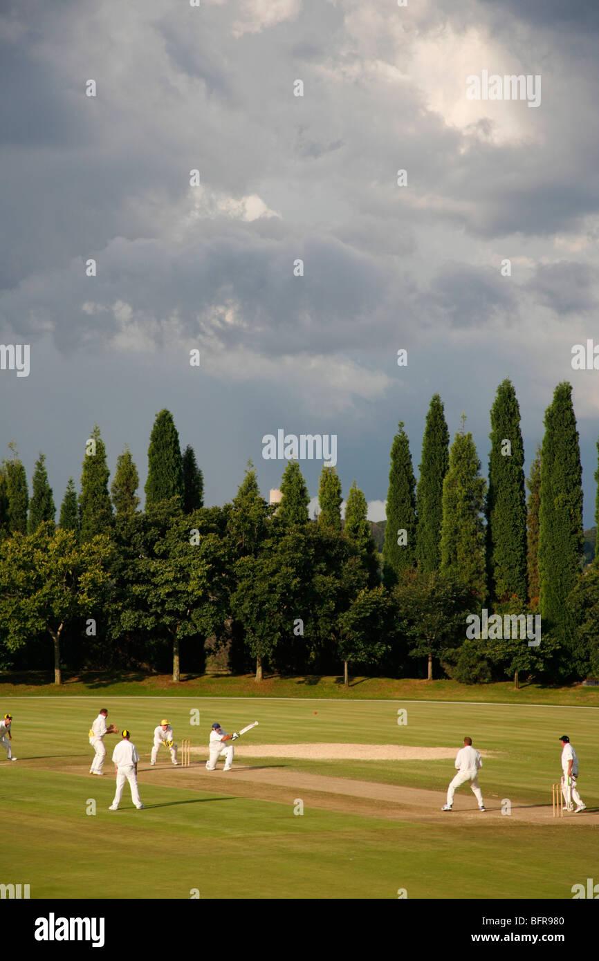 Una partita di cricket che viene riprodotto con un avvicinamento tempesta estiva Immagini Stock