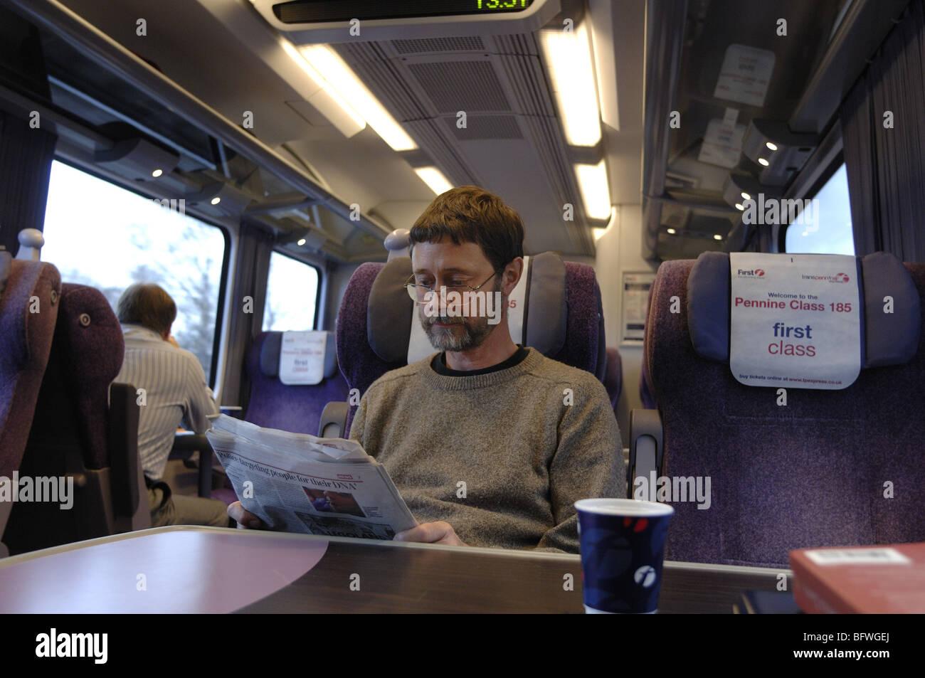 Il passeggero leggendo un giornale in una prima classe carrello di un treno in Inghilterra Foto Stock