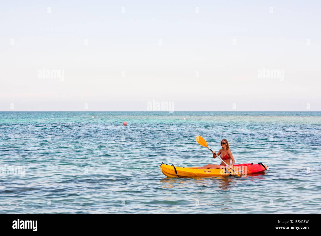 Giovane donna kayak tra le barriere coralline nell'Oceano Atlantico, Caraibi Cuba Immagini Stock