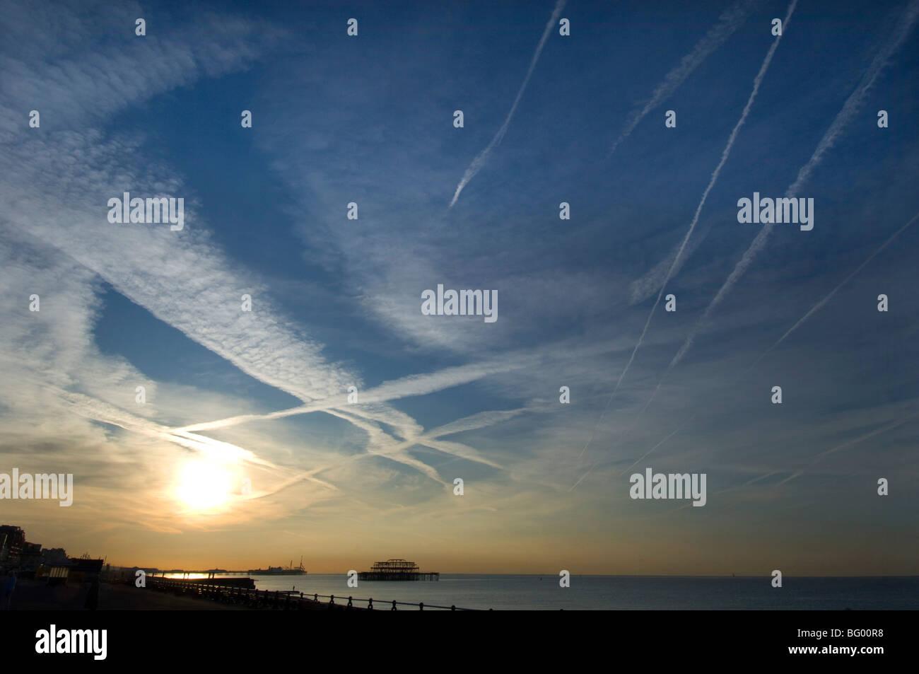 Alba sul lungomare di Brighton con jet striature nel cielo e il molo di ponente profilarsi in lontananza. Immagini Stock