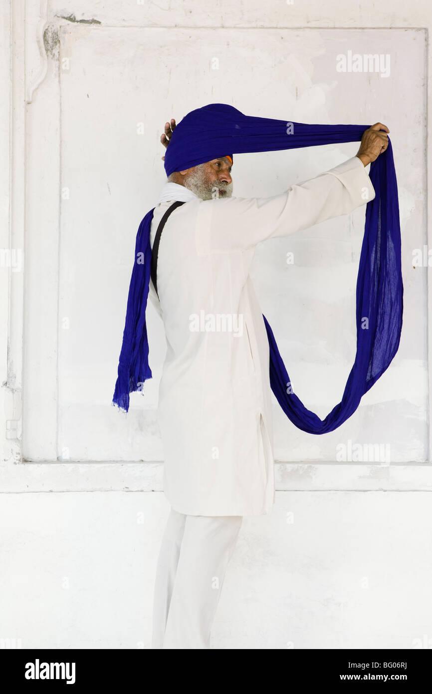 La religione Sikh l uomo che fissa il suo turbante nel Tempio d'oro, Amritsar e India. Immagini Stock